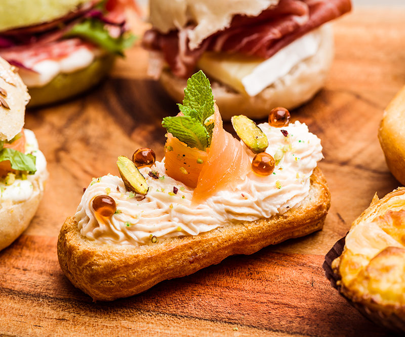 Savory eclair with salmon mousse, Bronte pistachios and balsamic vinegar drops